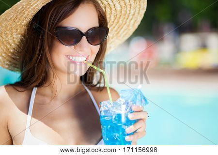 Smiling young woman holding a cocktail