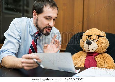 Businessman explaining a document to his teddy bear boss