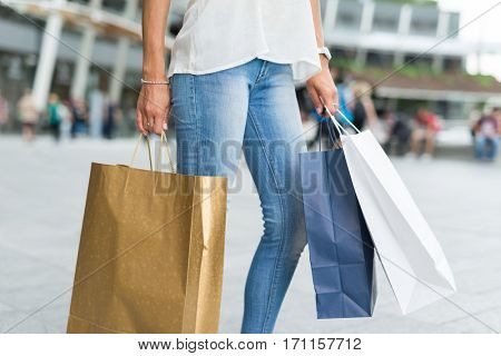 Detail of a woman holding shopping bags