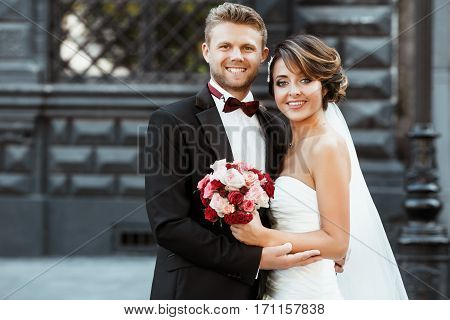 Wedding photo shooting. Bride and bridegroom smiling and embracing. Holding bouquet. Outdoor, waist up