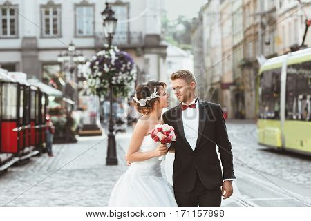 Wedding photo shooting. Bride and bridegroom walking in the city. Looking at each other, holding bouquet, embracing with one hand. Outdoor, waist up. Tram, cobbled street