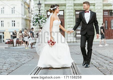 Wedding photo shooting. Bride and bridegroom walking in the city. Married couple holding hands of each other and bouquet. Outdoor, full body