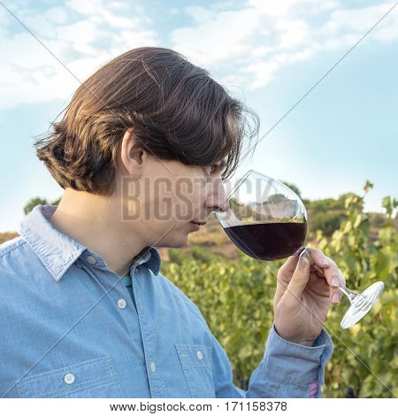 A square photo of a winemaker tasting his wine in a vineyard