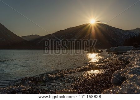 Colorful winter view of the sea the mountains the sun the ice on the shore and the sun glare on the water at sunset