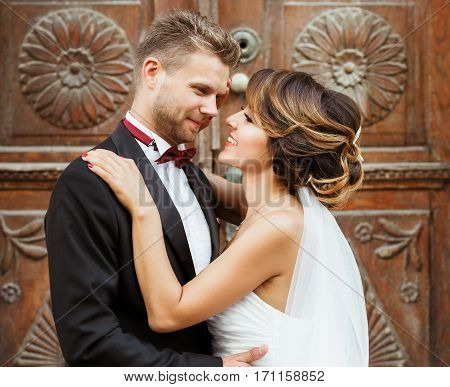 Wedding photo shooting. Bridegroom and bride standing near wooden door and embracing each other. Outdoor, waist up, closeup