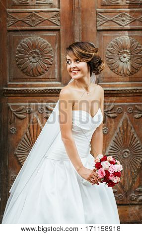 Wedding photo shooting. Bride standing near wooden door, looking aside and smiling. Wearing white dress and veil and holding bouquet. Outdoor