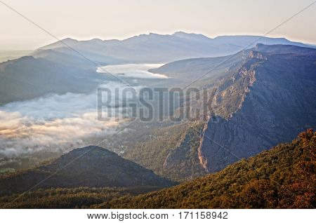 Clouds in the valley and the Wonderland Range  at sunrise - from the Boroka Lookout in the Grampians, Victoria, Australia
