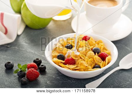 Cornflakes cereals with berries and milk pouring over