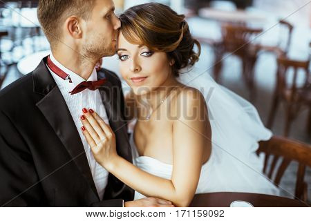 Wedding photo shooting. Bride and bridegroom sitting in cafe. Bridegroom kissing bride's forehead. Bride looking at camera. Outdoor, waist up, closeup