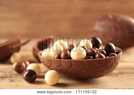 Chocolate Easter eggs and candies on wooden background