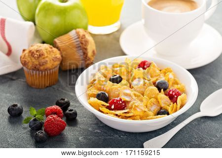 Cornflakes cereals with berries, orange juice and coffee for breakfast