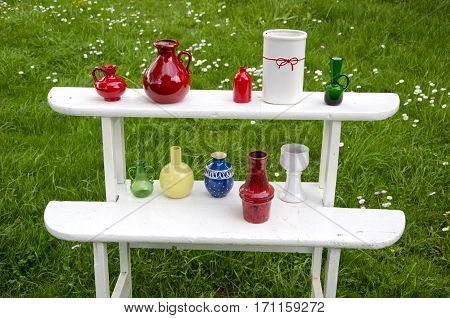white vintage wooden shelf in summer garden on grass and various vases
