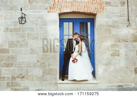 Wedding photo shooting. Bride and bridegroom standing near blue door, looking at each other and smiling. Outdoor, full body, profile