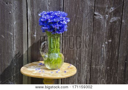 summer cornflowers in glass jug on table near old wooden barn wall
