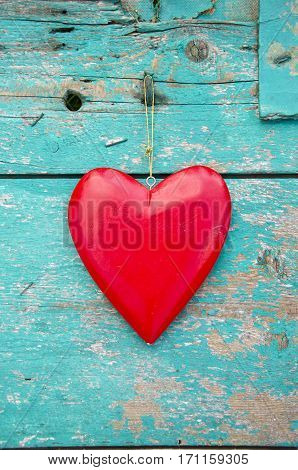 red heart hang on old textured green wooden wall background. Love symbol
