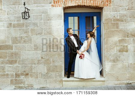 Wedding photo shooting. Bride and bridegroom standing near blue door, looking at each other and smiling. Leaning back from each other. Outdoor, full body, profile