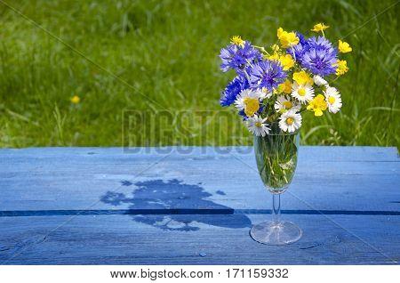 wild summer flowers in wineglass on blue old table in garden