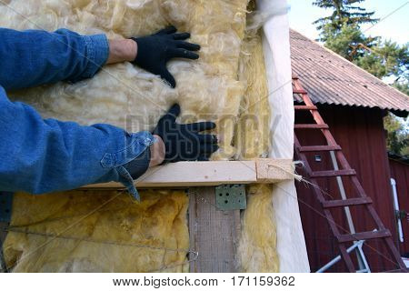 worker hands on house wall insulatiom material rockwool