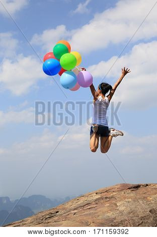 cheering young woman jumping with colorful balloon at mountain peak