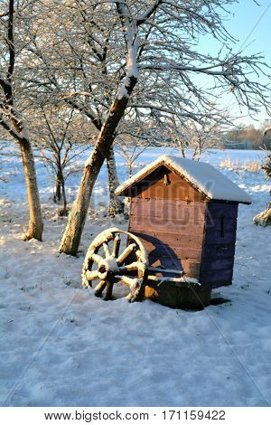 colorful beehive and horse carriage wheel on snow in winter garden