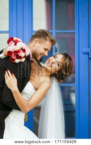 Wedding photo shooting. Bride and bridegroom standing near blue door and smiling. Embracing and leaning back, holding bouquet. Outdoor, closeup, waist up