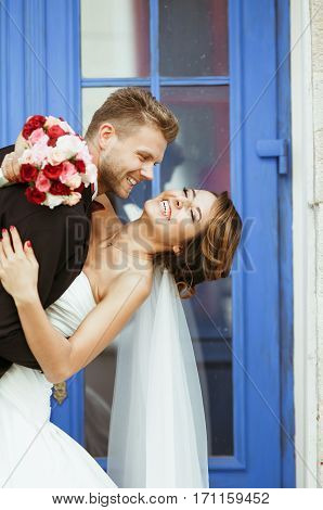 Wedding photo shooting. Bride and bridegroom standing near blue door and smiling. Embracing and leaning back, holding bouquet. Bride with closed eyes. Outdoor, closeup, waist up