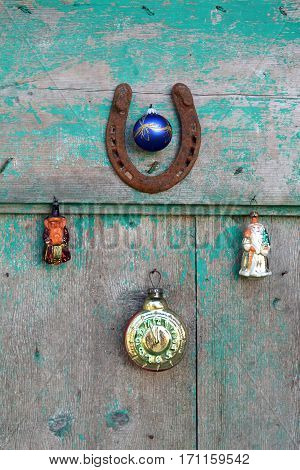 happy lucky Christmas and New year. Old rusty horseshoe Christmas snowman toys and vintage clock on wooden door