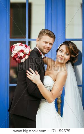 Wedding photo shooting. Bride and bridegroom near blue door. Embracing, holding bouquet. Looking at camera. Outdoor