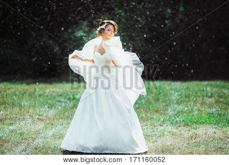 Wedding photo shooting. Bride under rain, holding her veil. Closed eyes. Wearing white dress and long veil. Outdoor, full body