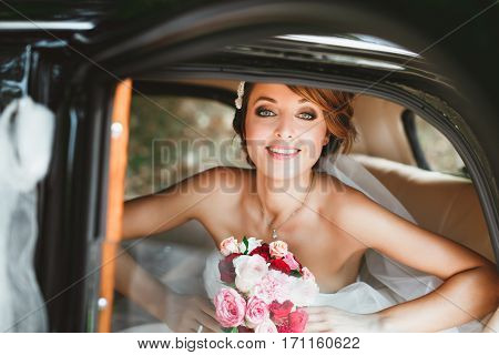 Wedding day. Bride sitting in wedding car, looking at camera, smiling and holding bouquet. Decorations. Waist up