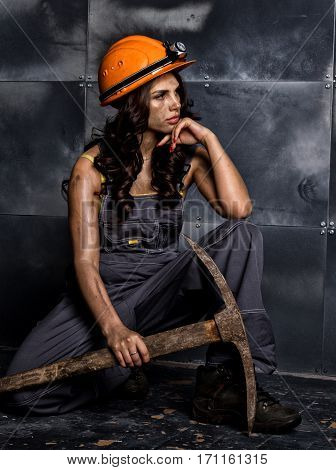 sexy female miner worker with pickaxe, in coveralls over his naked body, sitting on the floor on backdrop of steel wall.