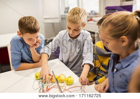 education, children, technology, science and people concept - group of happy kids playing with invention kit at robotics school lesson