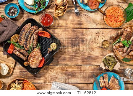 Outdoors Food Concept. Frame of Different foods cooked on the grill on the wooden table grilled steak grilled sausage and grilled vegetables. Top view