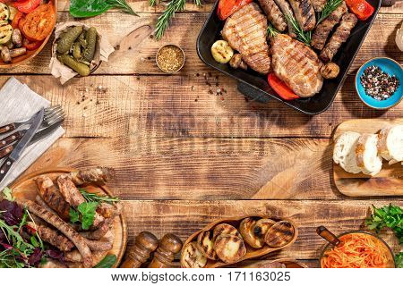 Frame of Different foods cooked on the grill on the wooden table on a sunny day grilled steak grilled sausage and grilled vegetables. Top view. Outdoors Food Concept
