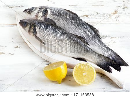 Two Raw Seabass With Lemon On A Wooden Background.