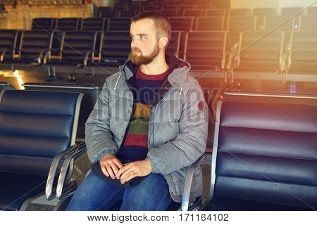 A passenger waits for his flight at the airport. Rows of seats in airport waiting room. Concept travel. A young man with a beard.