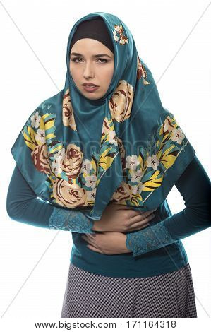 Female wearing a hijab conservative fashion for muslims middle east and eastern european culture. She is isolated on a white background and holding her stomach because of pain or sickness