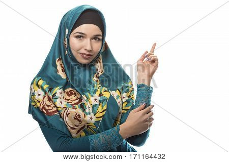 Female wearing a hijab conservative fashion for muslims middle east and eastern european culture. She is isolated on a white background and advertising something.
