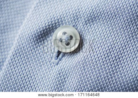 clothing, formal wear, fashion and objects concept - close up of blue shirt button