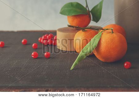 Juicy tangerines and red current on wooden table