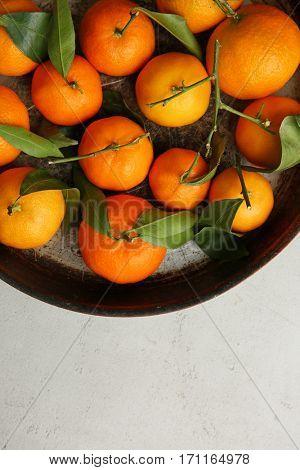 Juicy tangerines in bowl on grey background