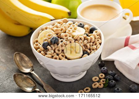 Healthy cold cereal with banana and blueberry in a white bowl, quick breakfast or snack for children
