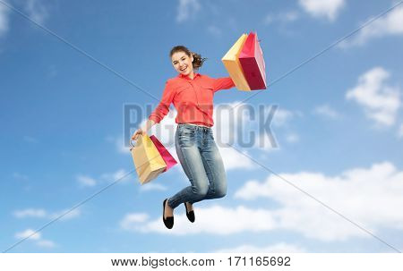 sale, motion and people concept - smiling young woman with shopping bags jumping in air over blue sky and clouds background