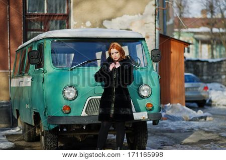 Young Red Haired Girl Posed On Checkered Dressand Fur Coat Background Old Retro Cyan Minivan.