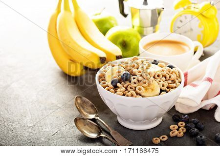 Healthy cold cereal with banana and blueberry in a white bowl, quick breakfast or snack for children with copyspace