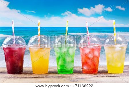 Colorful Cold Drinks In Plastic Cups On The Beach