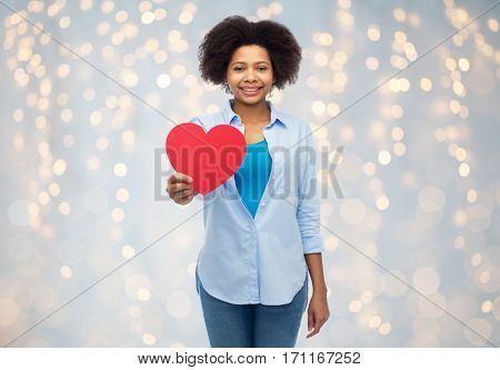 people, love, valentines day and health concept - happy african american young woman with red heart shape over holidays lights background