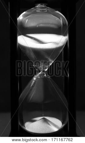 Time passing concept. Black hourglass with white sand on dark background
