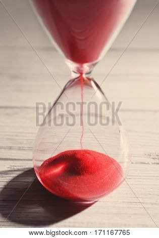 Time passing concept. Crystal hourglass with red sand on light wooden background