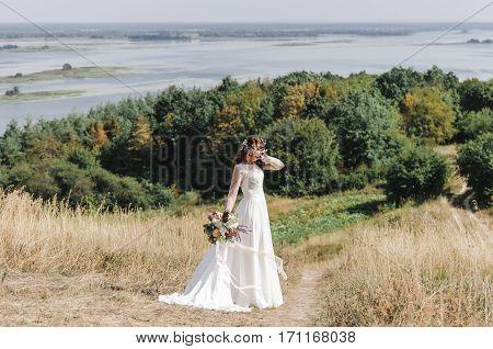 Невеста в свадебном платье на горе с видом на просторный разлив реки